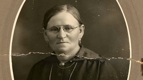 A woman is sitting for her photo. It is in black and white and she is wearing glasses, a necklace and has her hair pulled back.