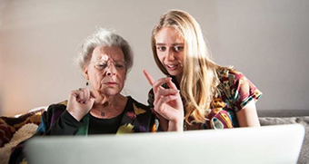An older woman with furrowed brow and younger woman mid-speech concentrate on a computer screen.