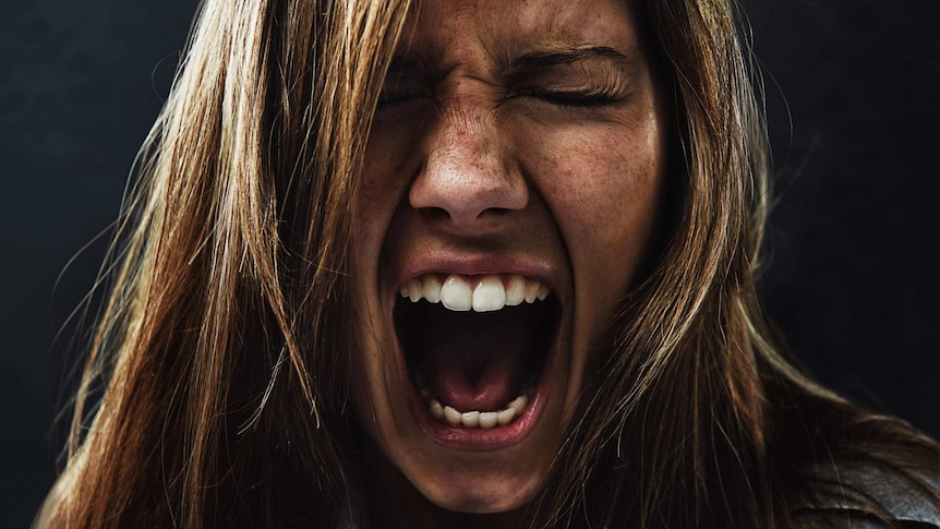 Close up of woman's face in a silent scream.