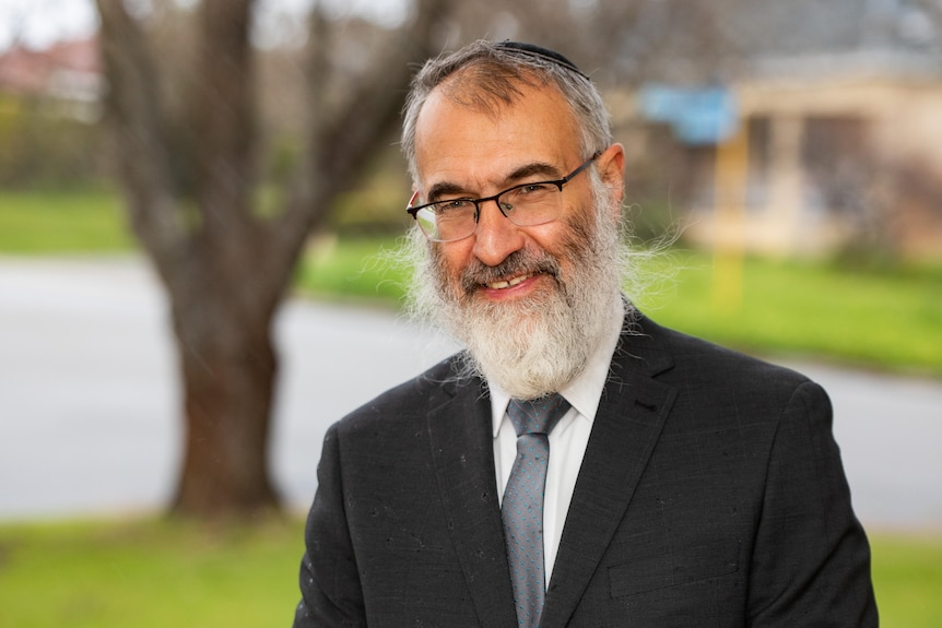 A head and shoulders profile shot of Rabbi Marcus Solomon posing for a photo smiling outdoors.