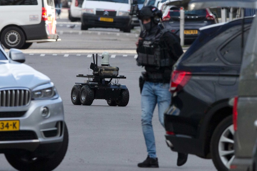 Looking down a street cordoned off with red and white police tape, an autonomous police robot drives between cars and officers.