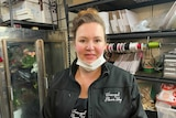 A woman with a face mask around her chin inside a florists