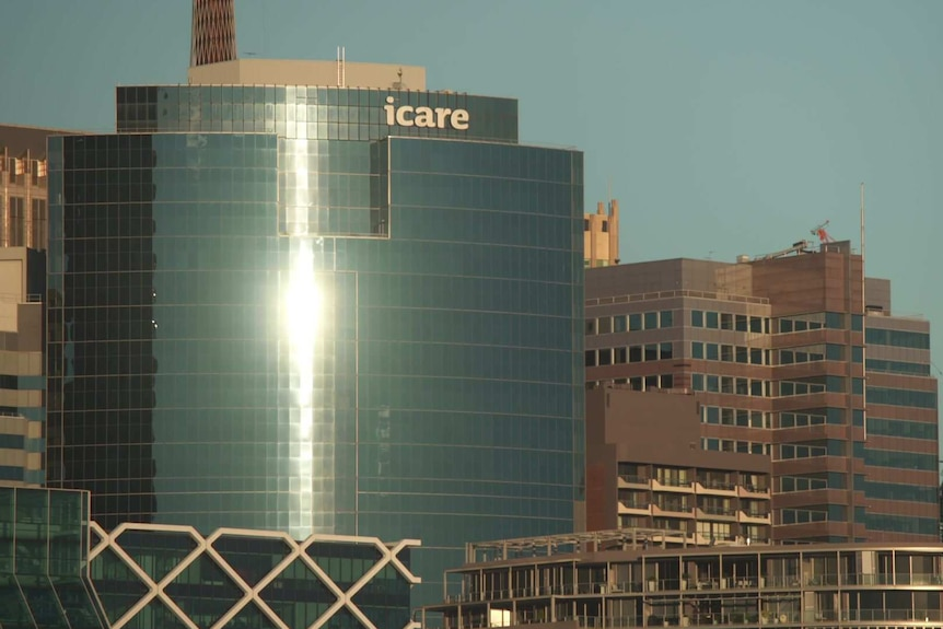 Afternoon sun reflecting of the windows of a building with an icare at the top.