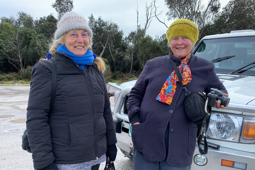 Two older women stand next to a car