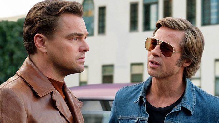 Two men stand in the street, one looks away with serious expression while the man wearing sunglasses faces him and speaks.
