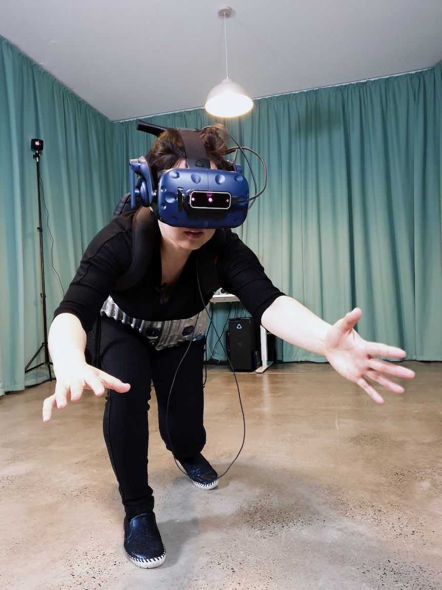 Artist Eugenie Lee with a VR headset and haptic belt on in a room with curtains in the artwork Breakout My Pelvic Sorcery