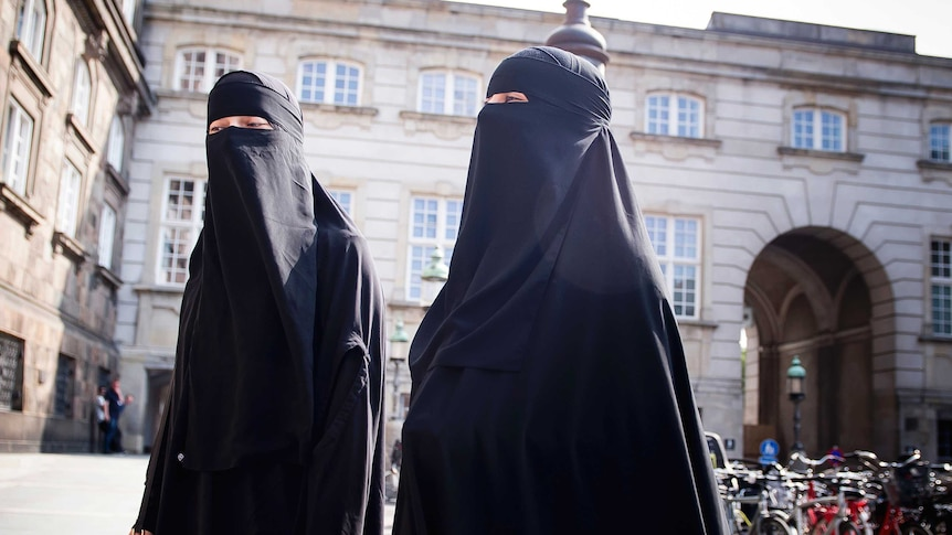 Women in niqab walk, in front of the Danish Parliament at Christiansborg Castle.
