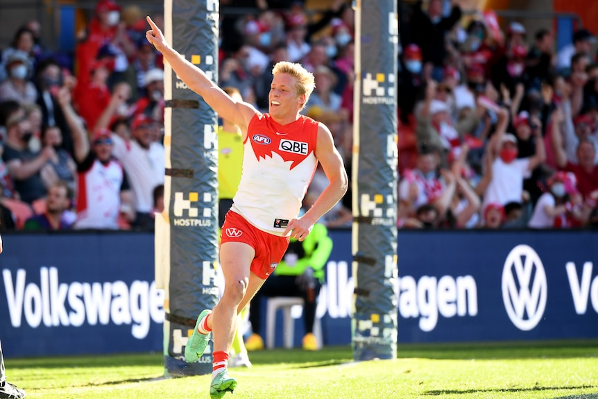 A blonde haired man in white and red jersey raises arm in celebration in front of stadium crowd