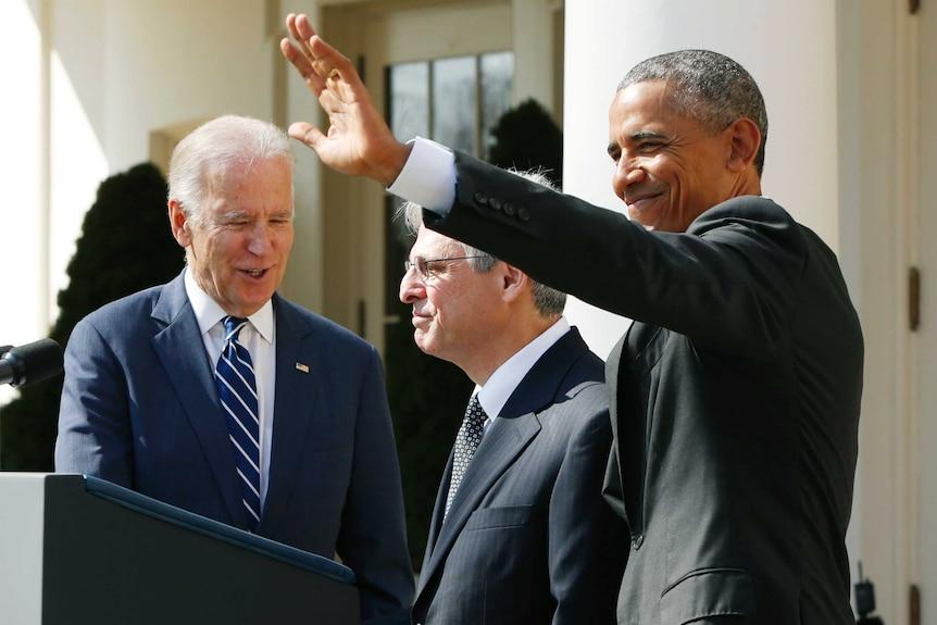 Barack Obama waving while Joe Biden speaks to Merrick Garland