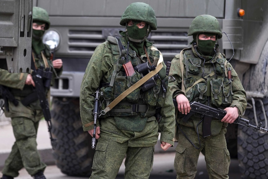 Troops stand near Russian army vehicles in Crimea