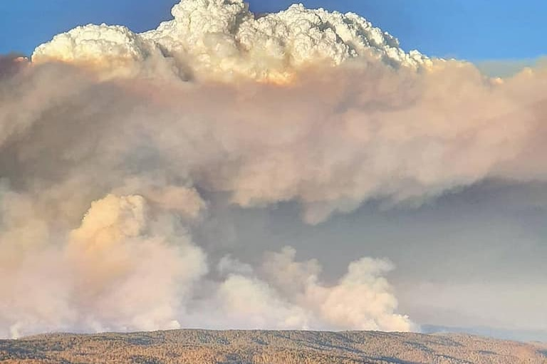 A huge smoke cloud over a large landscape of hills and trees.