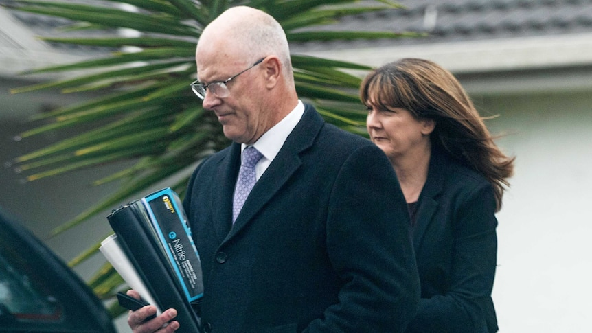 A man and a woman walk towards a car, holding binders and folders under their arms.