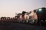 A train at sunset, full of iron ore on a remote track