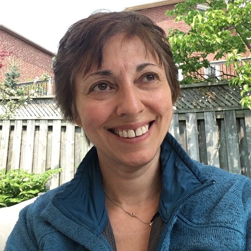 A woman with short hair smiles broadly while looking at the camera.