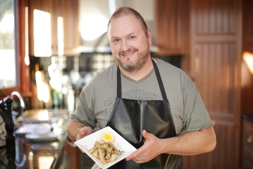 Chef James Maffescioni standing in a kitchen holding a plate of cooked squid to depict how to prepare and cook squid.
