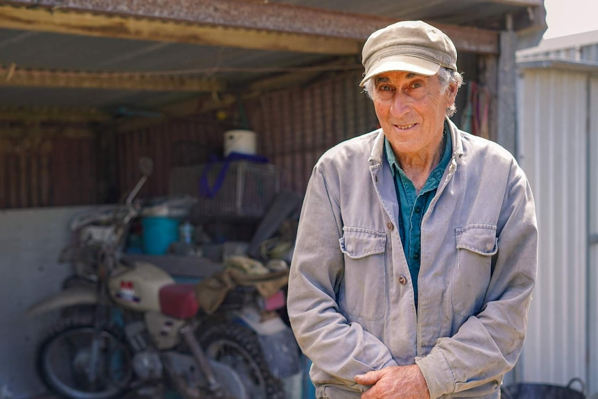 An older man in a grey cap smiles at the camera, a motorbike and shed behind him.