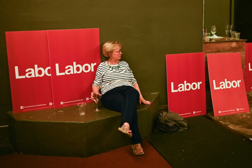 A Labor party supporter is seen in an empty room on election night.