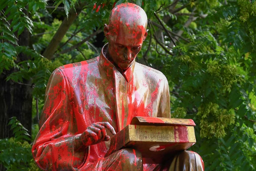 Statue of man at typewriter in park covered in red paint