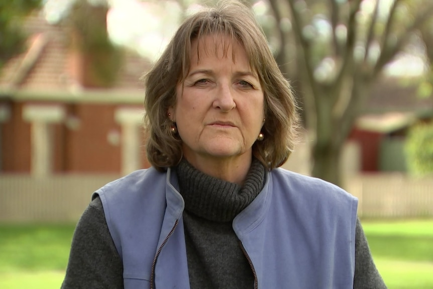 A woman with a grey turtleneck jumper and a blue fleece vest stands in a park, with houses in the background