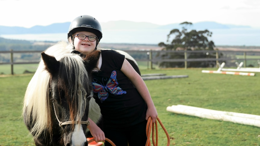 Young girl leans on pony at riding arena surrounded by rolling green hills.
