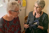 Two woman with short grey hair sitting in a kitchen talking.
