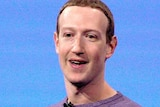 Mark Zuckerberg stands and gives a speech at a conference