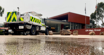 A CFA truck is parked in the Bairnsdale Incident Control Centre, as water runs along the driveway from rain.