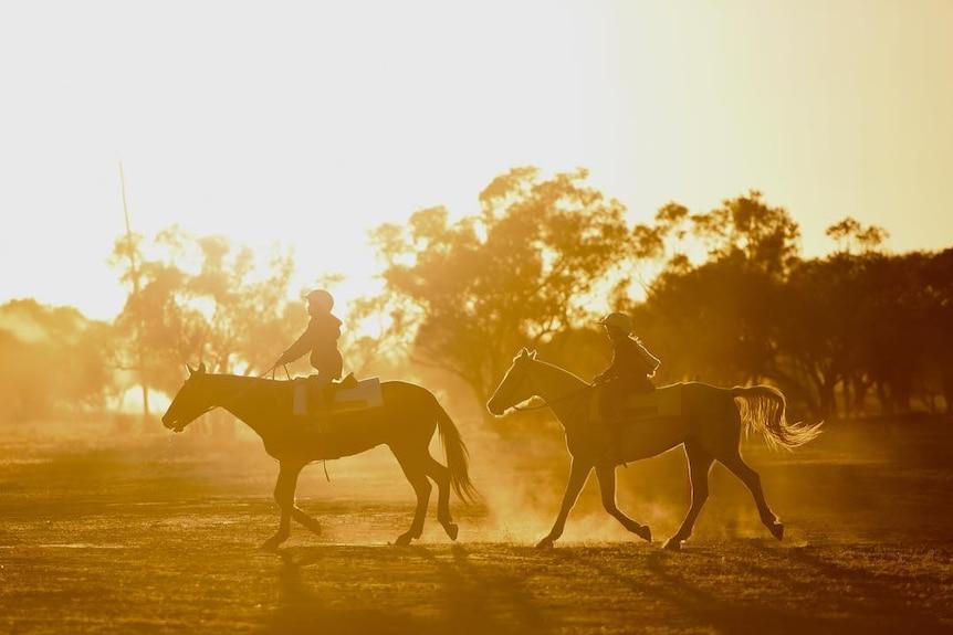 在昆士兰偏远的小镇Yaraka,两个孩子在朝阳中骑着他们的小马去竞技场。