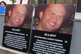 Two posters sit side-by-side on a ledge outside a court showing the face of a man who died and his DOD.