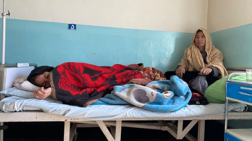 A girl lies in a hospital bed with a red blanket on top of her as a woman watches on.