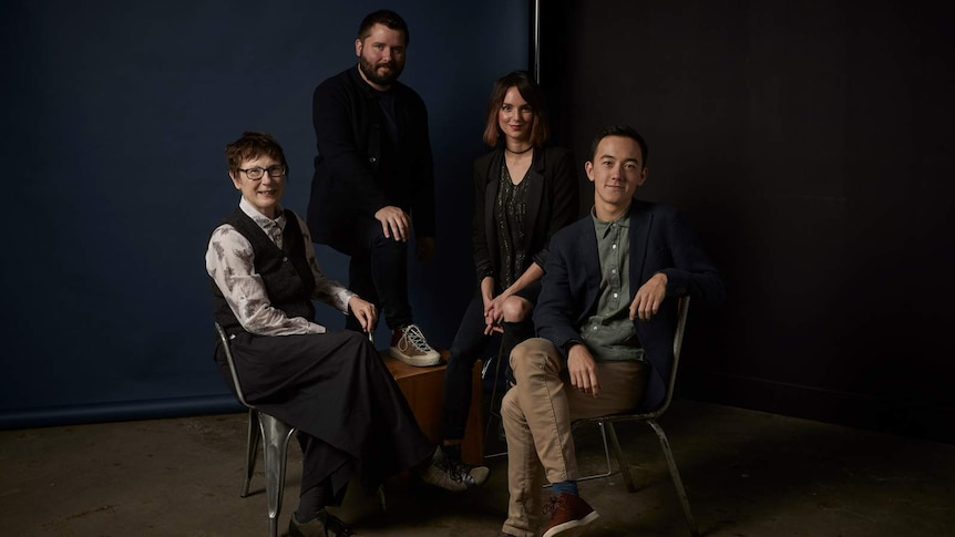 The four theatre makers pose on chairs in front of a moody, navy blue background.