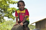 A boy wearing a colourful shirt sitting on a tyre stuck upright out of the ground.