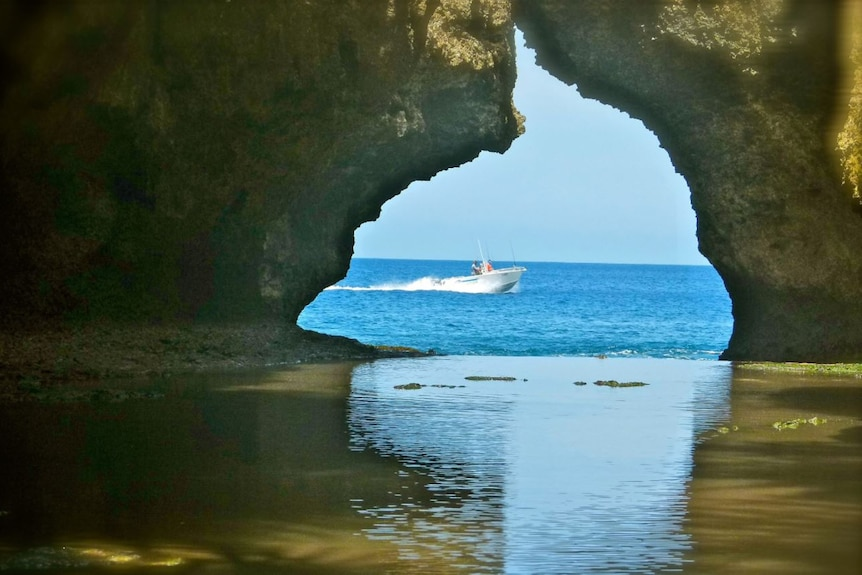 A small boat, seen through a pair of overhanging rock formations, makes its way out to sea.