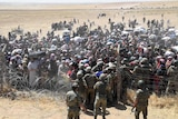 Turkish soldiers help Syrian refugees as they cross the Turkish-Syrian border