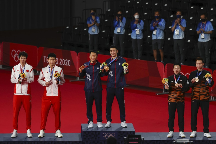 The badminton teams stand on the podiums with their medals.