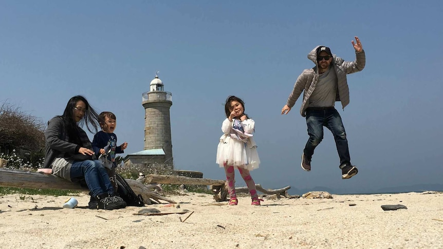 A family on the beach with the father jumping in the air, the daughter giving a peace sign, and the mother and son smiling