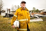 Peter Heward wearing a firefighting jacket holds a helmet with his name written on it.