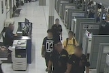 The two boys are escorted by officials in Sydney airport