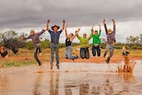 Adults and kids jump in air with puddle of water beneath them.