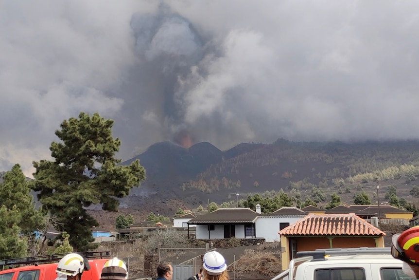 people watch from a distance while a volcano erupts