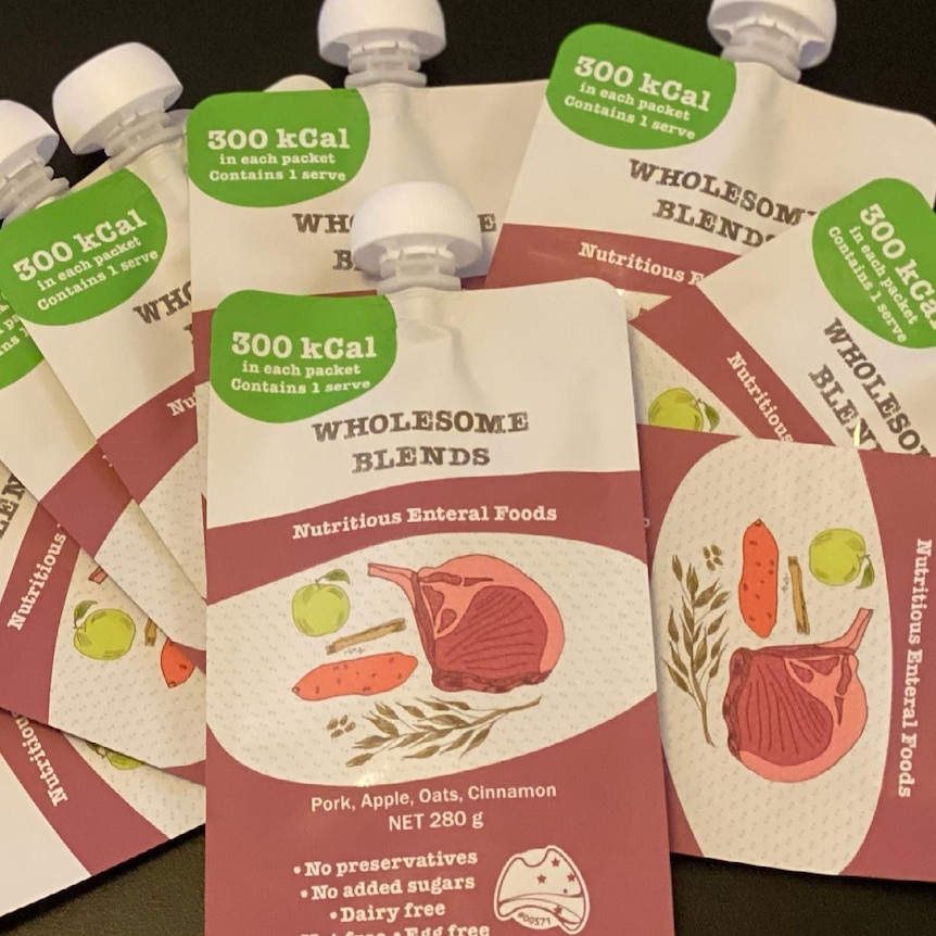 Rose pink and white pouches of enteral products, blended meals with drawings of meat and vegetables.