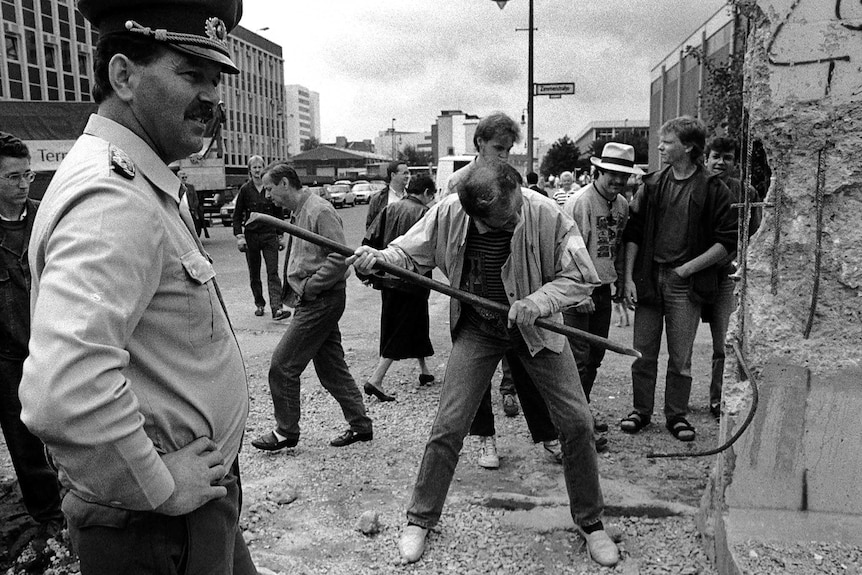 An East German border soldier watches a man hammering a section of the Berlin Wall near Checkpoint Charlie.