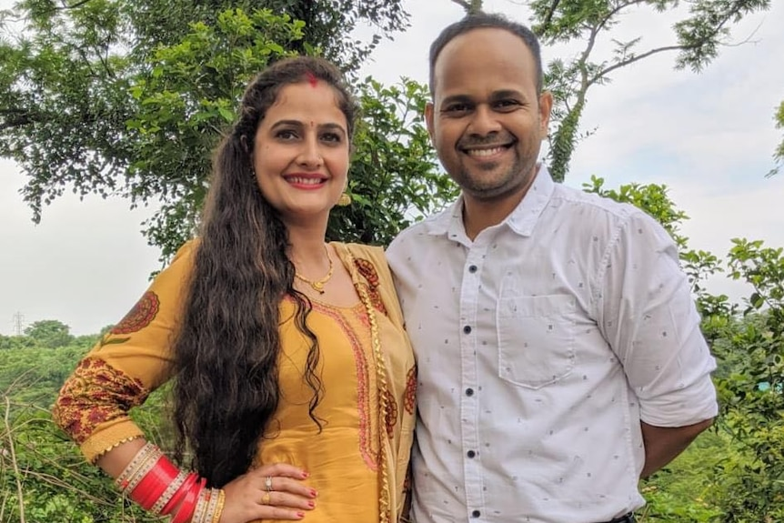 Queenslanders Neha Soni and Shailesh Thorat smile at the camera while standing outside