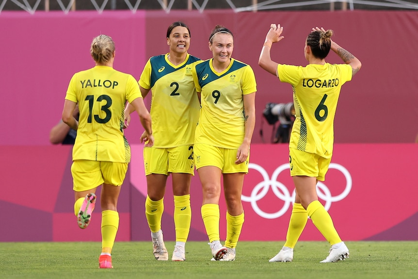 Sam Kerr and Caitlin Foord smile while teammates run up to high five them