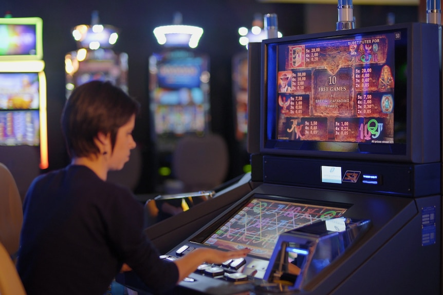 Anonymous woman sitting at electronic gaming machine.