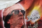 A poster of Libyan ruler Moamar Gaddafi burns during a demonstration in the north-central Libyan tow