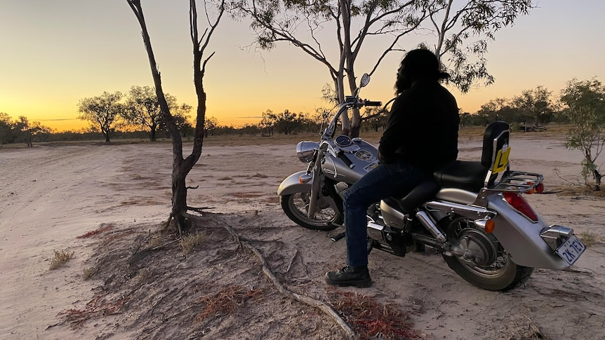 A silhouette of a man on a motorbike with a sunset in the background.