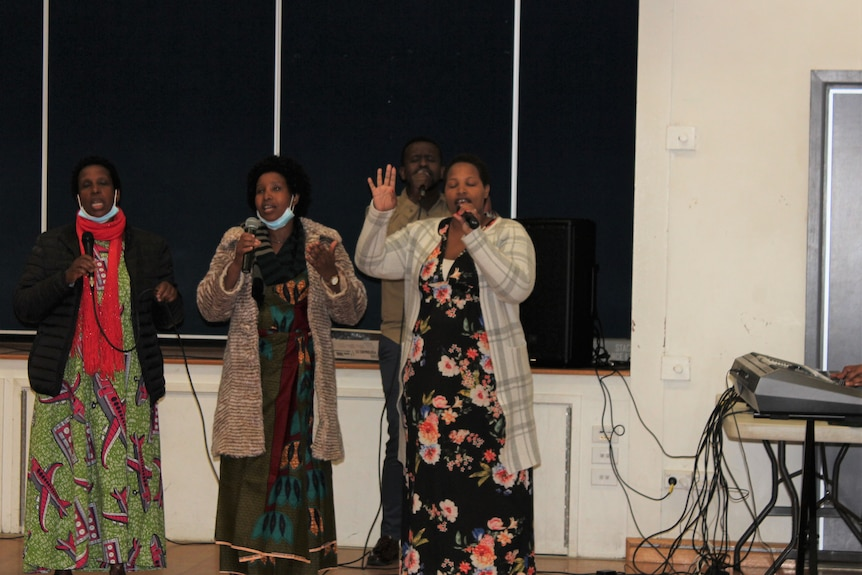 Women sing in a an indoor sports centre.