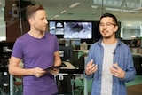 Two men in a room of computers and TV screens talk to one another