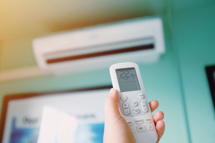 Person pointing remote at reverse cycle air conditioner